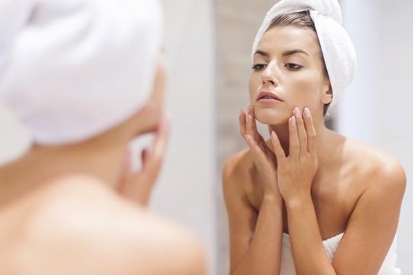 женщина с полотенцем на голове смотрит на свое лицо