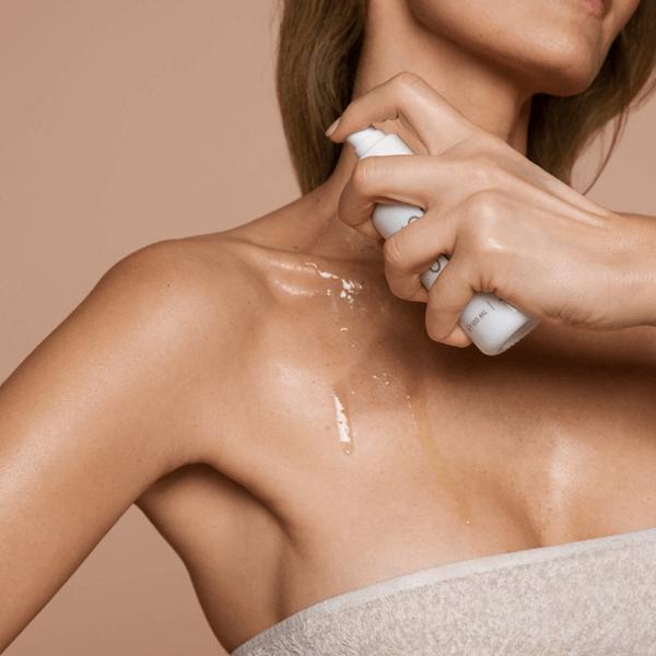 женщина наносит масло на тело
